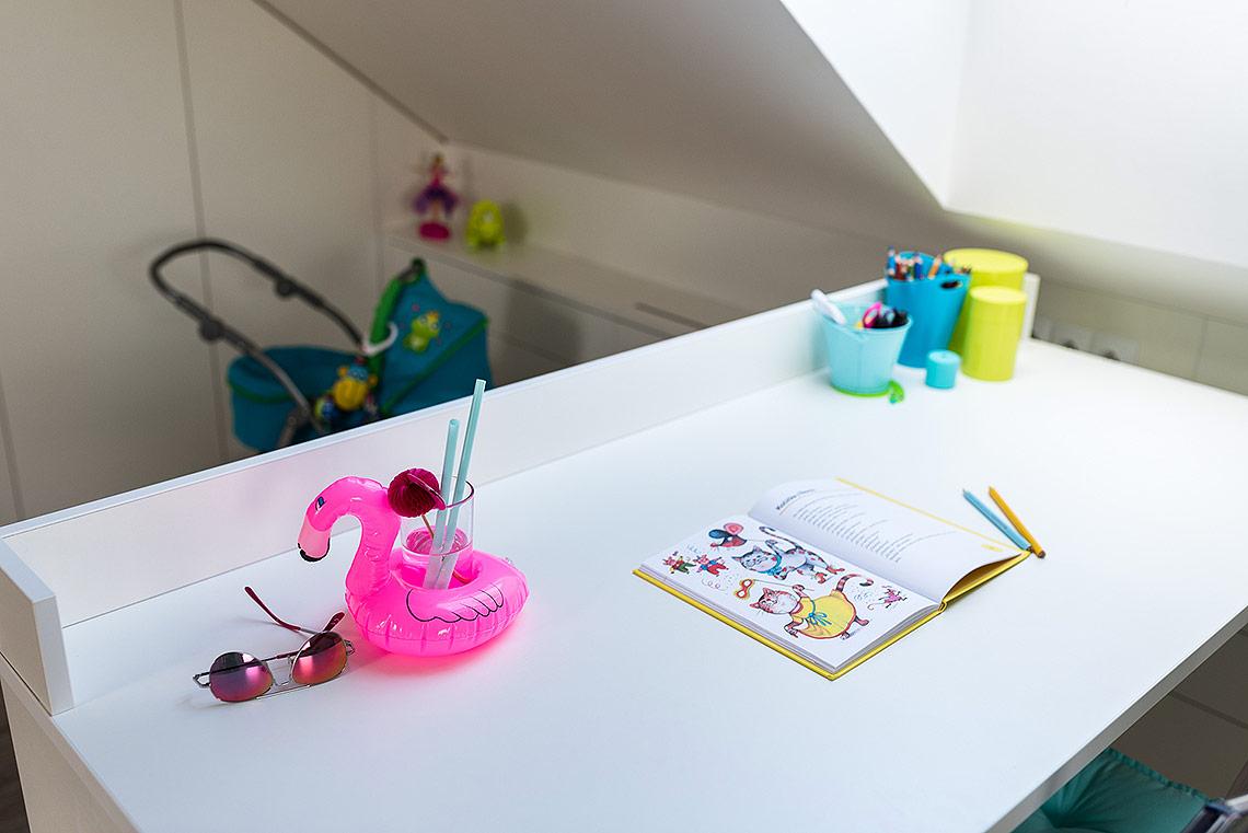 Psací stůl vpokojíčku je usazen vkolejničce, díky které ho lze zafixovat ve dvou polohách