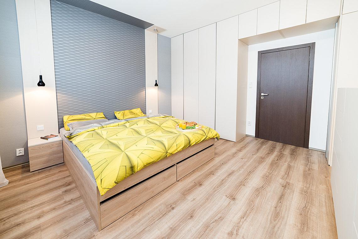 Tapeta splastickým vzorem nahrazuje klasické čelo postele