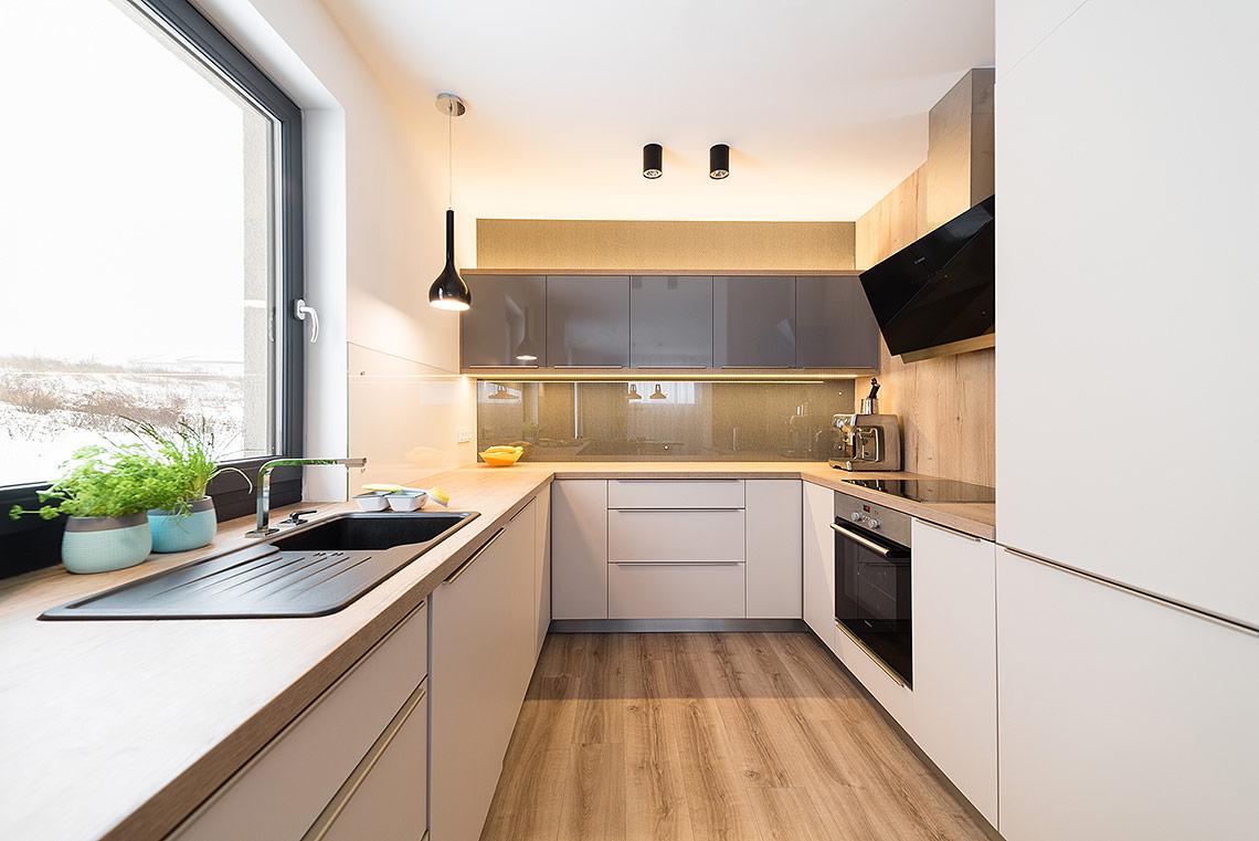 Kuchyňský kout materiálově navazuje na obývací pokoj vkombinaci dřevo – béžová – antracitová