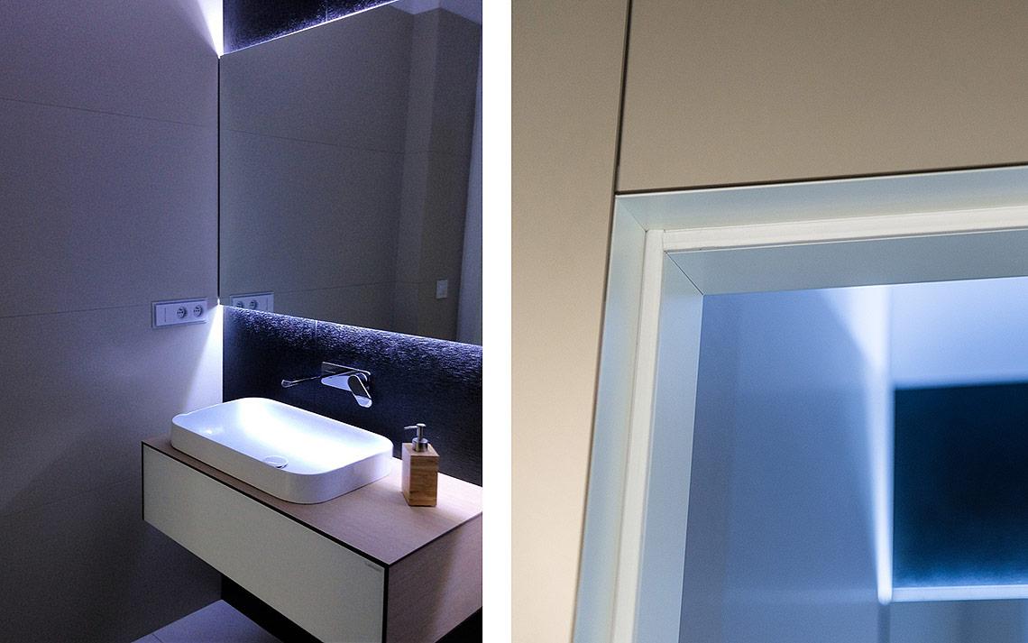 Koupelna svelkoformátovým obkladem a nepřímým osvětlením. Detail napojení skel a dveří.
