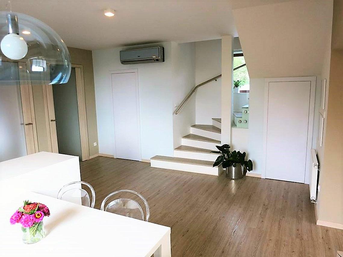 Schodiště do patra, dveře do spíže a komory splývají sbílou stěnou a mají dotykové otvírání